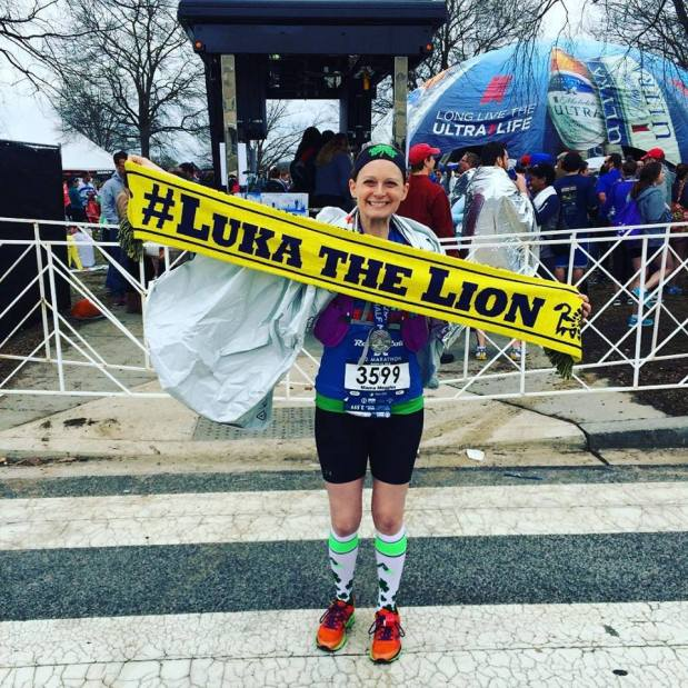 Megan holding a luka the lion banner